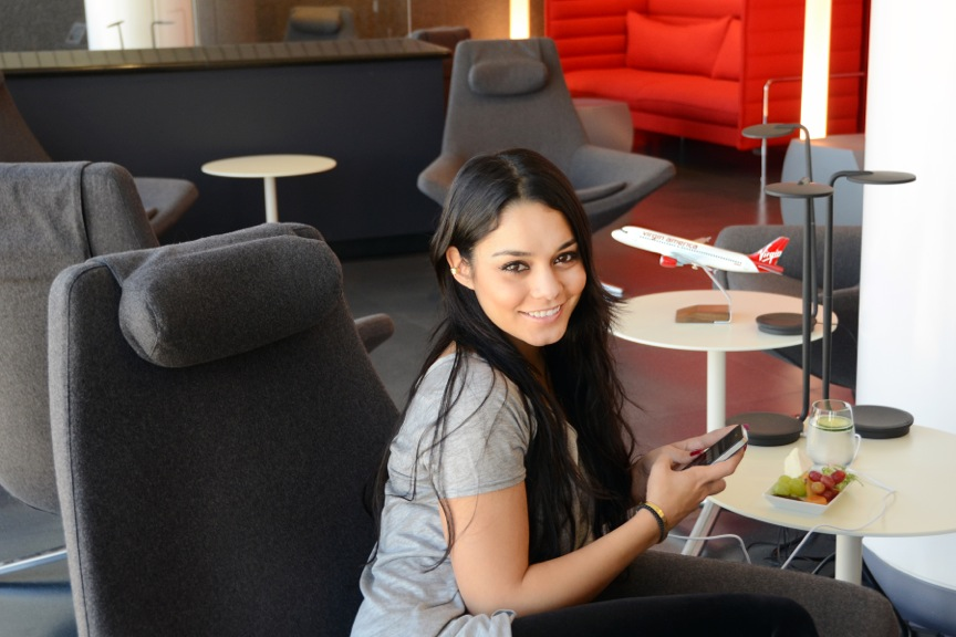 "Vanessa Hudgens relaxes before a flight to JFK at the new Virgin America Loft at LAX. According to Virgin America, the chic space ""extends the airline's signature cabin experience into the airport space with amenities like a cocktail bar and dining experience with a Virgin twist – including a 'Lofty Libations' artisanal cocktail selection – featuring the 'Virgintini' and 'Mile-High Margarita.'"