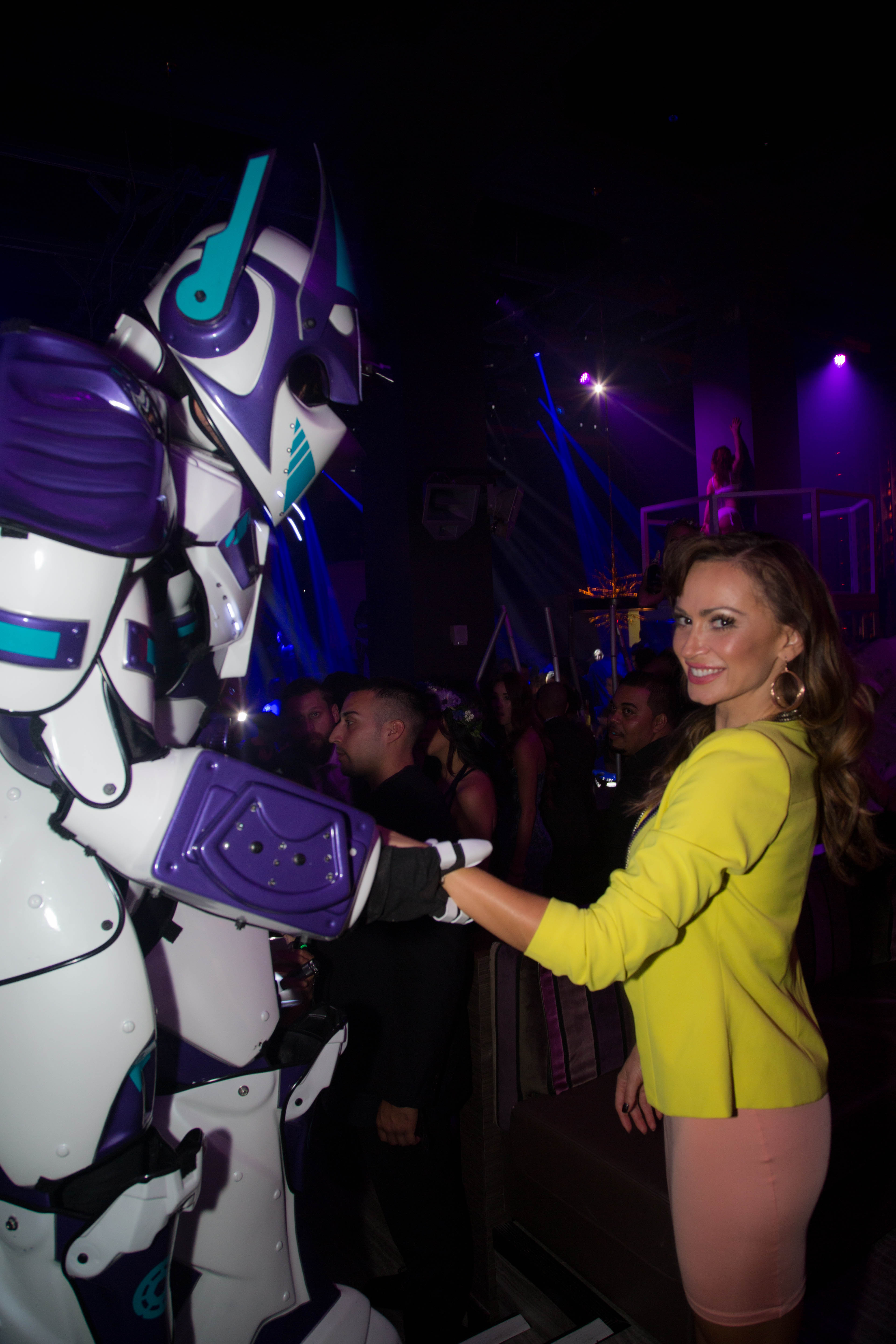 Dancing with the Stars' Karina Smirnoff (in a vintage dress, Lumier by Bariano jacket and Carlo Pazolini shoes) gets acquainted with Parq Restaurant & Nightclub's 10-foot-tall foot robot — aka Parq Rocatron — at its grand opening on Oct. 25. (Julien Jollon)
